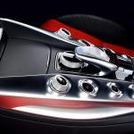 The stylish center console with aluminium elements between black and red sports auto chairs