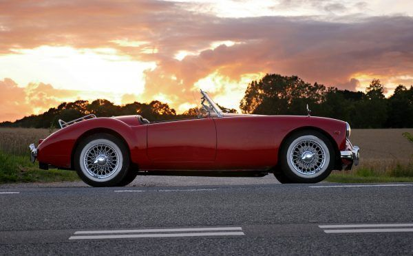 Beautiful red old cabriolet with white tires on the road against a cloudy sky
