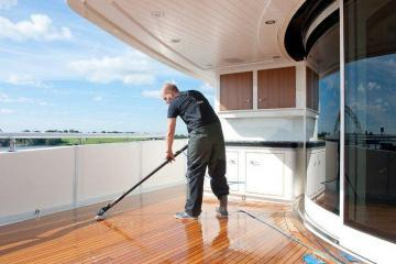 man cleaning yacht